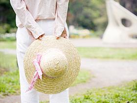 麦わら帽子を持つ女性の後ろ姿